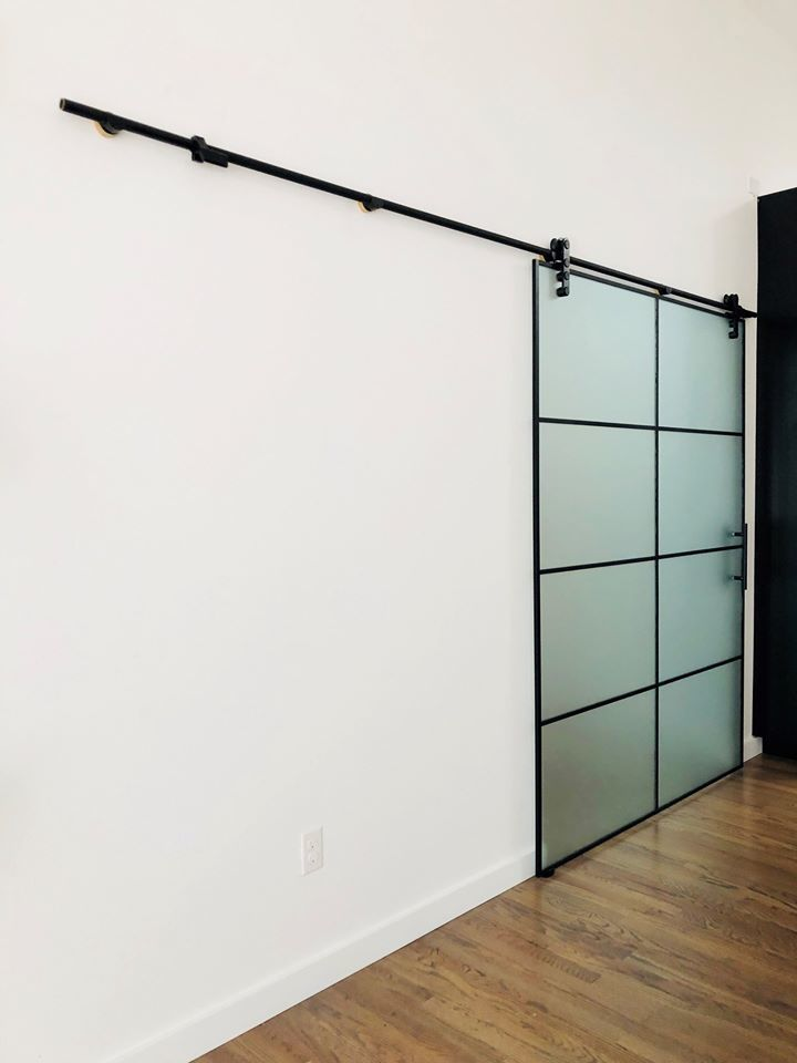 Denver Glass Interiors made this custom heavy sliding glass door.  The glass is Acid Etched to allow light to pass, but also provides privacy.