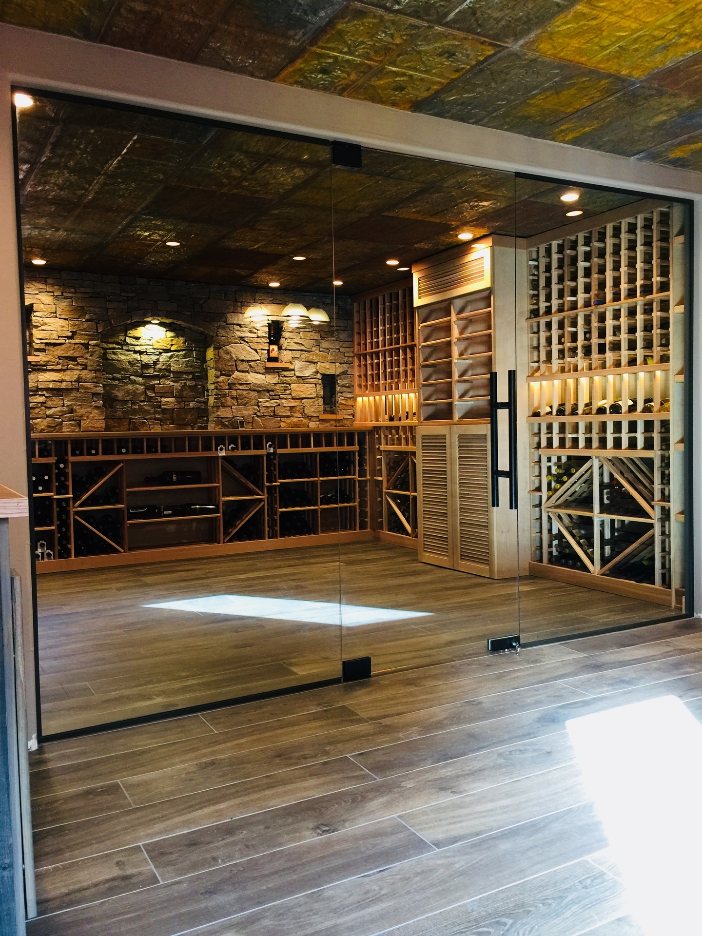 """1/2"""" clear tempered glass wine cellar system. Denver Glass Interiors used a unique design with mitered overlapping vertical edges of the door and panels."""