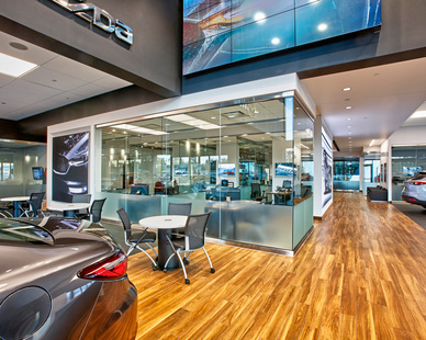The Mazda showroom floor at the new dual Luther Mazda Mitsubishi Dealership in Brooklyn Park, Minnesota features rich wood accents and modern frameless glass walls.