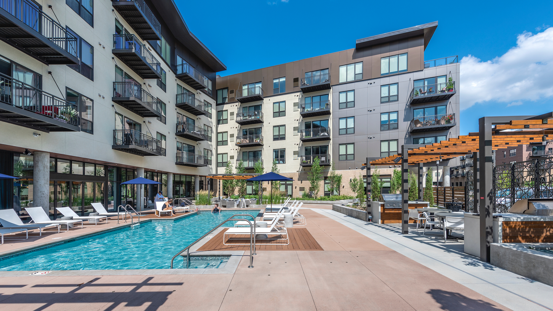 The modern outdoor pool area at Parkway 25, featuring outdoor amenities and chaise lounge chairs for a relaxing experience.