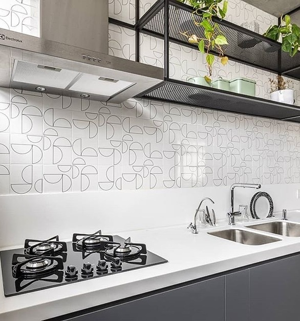 Beautiful pure white counter mixed with abstract tile makes for the perfect addition to this renovated apartment kitchen.