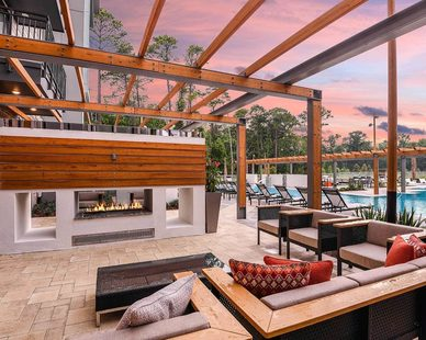 The comfortable outdoor fireplace at the outdoor swimming pool area at the JTB Apartments in Jacksonville, FL, by Dwell Design Studio.