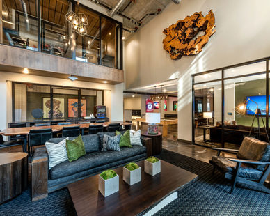 The high ceilings allow for unique interior design with an incorporated mezzanine level that oversees the lobby at The Point at Ridgeline by Dwell Design Studio.