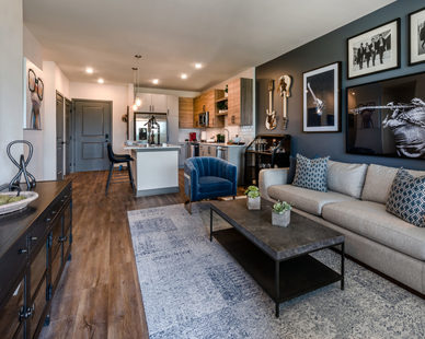 A living room design at The Point at Ridgeline, featuring premium wood floors and unique wall decor.