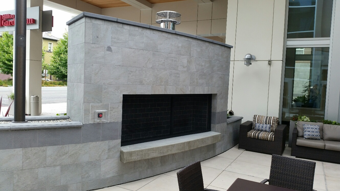 An outdoor fireplace was added as part of a safety wall to the outdoor patio at a Hilton Garden Inn.