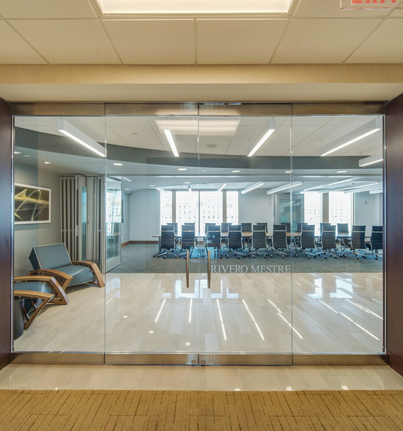 Glass doors and walls create an open feel and allow natural light to fill the space for a healthy workspace. LegArm custom lounge chairs were used for the guest waiting area in this project.