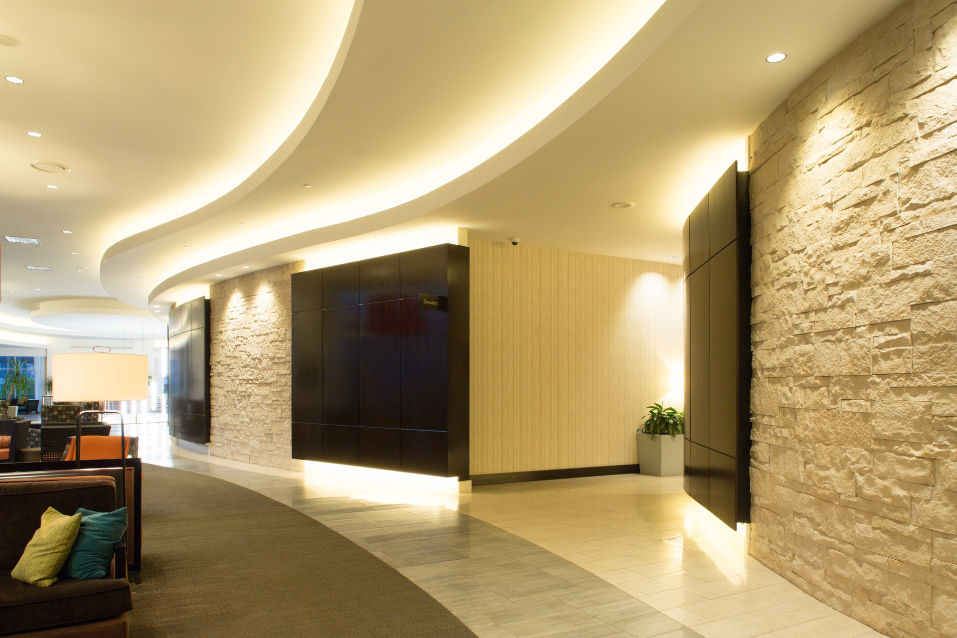 Beautiful corridor showcasing a custom ceiling along with the multi-dimensional Cut Coarse Stone by Eldorado Stone in Oyster.