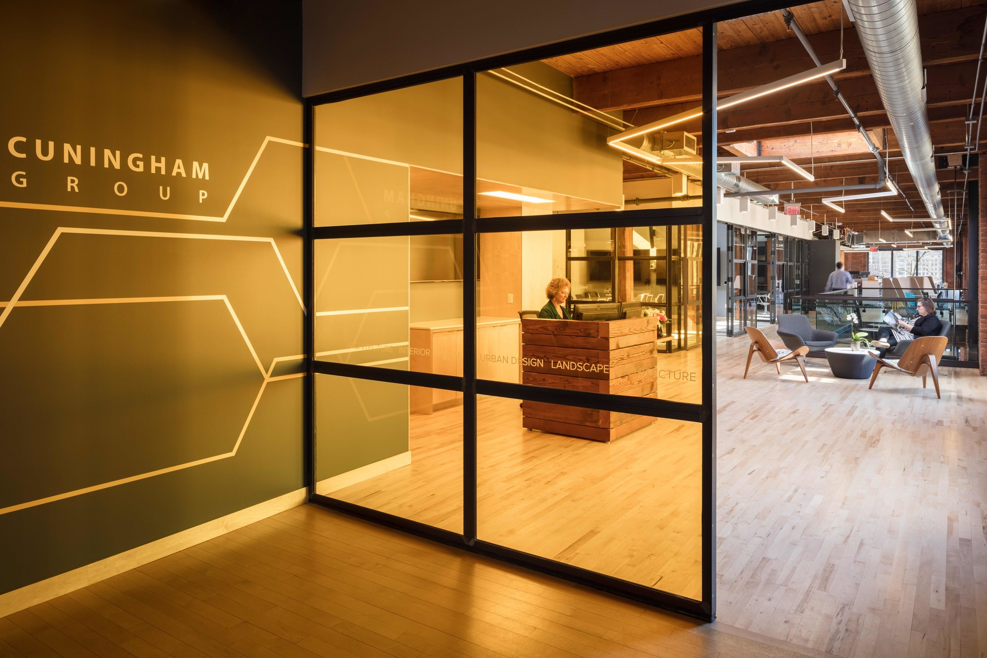 The beautiful entrance into the office featuring warm tinted glass and high-end finishes provides a welcoming atmosphere for guests and visitors.