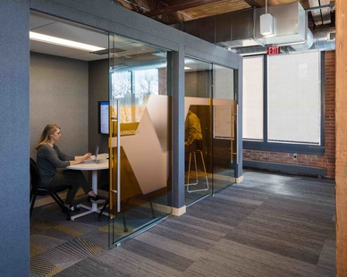 The architectural glass walls provide privacy and modern design cues for small office meeting rooms throughout the space.