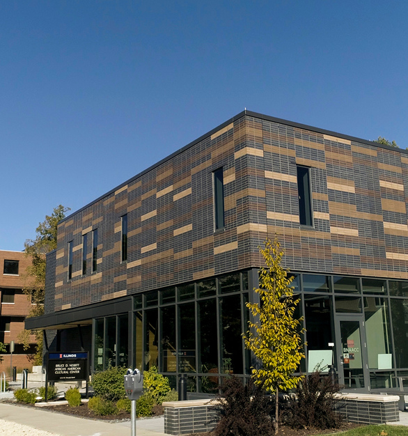 """The solid brick envelope of the Cultural Center expresses the strength and resiliency of the African American community, while the large glass expanses on the first level demonstrate the AACC's mission for openness and inclusiveness. It was important that the facility reflect African American heritage, while remaining consistent with the overall aesthetic of the neighboring quad and the campus as a whole. The main entrance is made up of two sections of brick – one dark gray to represent the """"strength and guidance"""" that the University of Illinois provides for its students and one in varied colors of tan, brown and gray, representing the """"multi-toned hues"""" of students, according to project architect Dina Griffin, a 1986 University of Illinois graduate."""