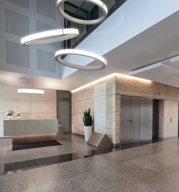 Guests are welcomed by Compass, ceiling suspended elegant shaped luminous halos by Eureka, in this modern reception.