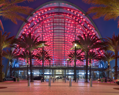 Lined with palm trees, the Anaheim Regional Transportation Intermodal Center (ARTIC) features large structural glass glass walls and red lights. This photo was captured by Ferrari Images.
