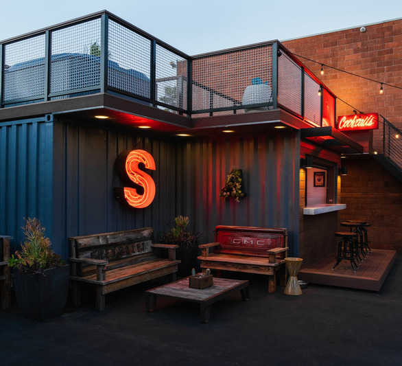 Art's Steedle's goal with his container bar project was to create a space at his shop where his team could unwind at the end of the day and enjoy the bar, sit in the hot tub or lawn chairs, and chat about the day.  Photography Credit: Attila Adam Photography