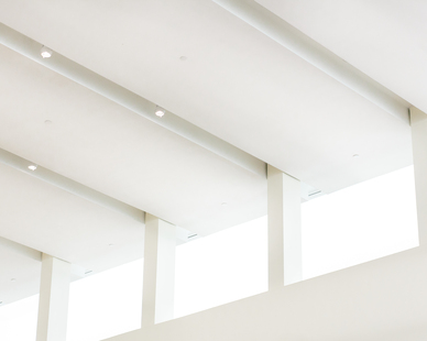 Minimalist, white ceiling using Fellert's Even Better Silk to help with sound absorption.