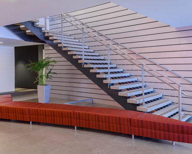 Custom floating staircase with cable railing and concrete treads.