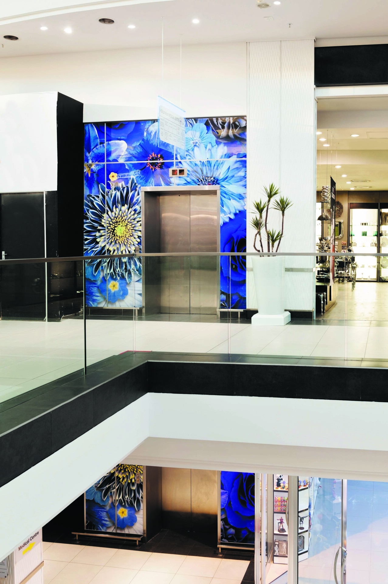 Add personalization or branding with beautiful wall graphics.  This shopping center used a floral design to create a easy way for shoppers to spot the elevators.  Fusion can elevate your brand or personalize your home on any budget. By combining our ever-expanding line of graphics or your own artwork with our more than a dozen substrate options, you can make a unique, custom design perfect for your business or home.   You can use Fusion for such applications as wall art, divider panels, displays, and large format murals allowing you to stand out from the crowd. Your imagination is the limit!