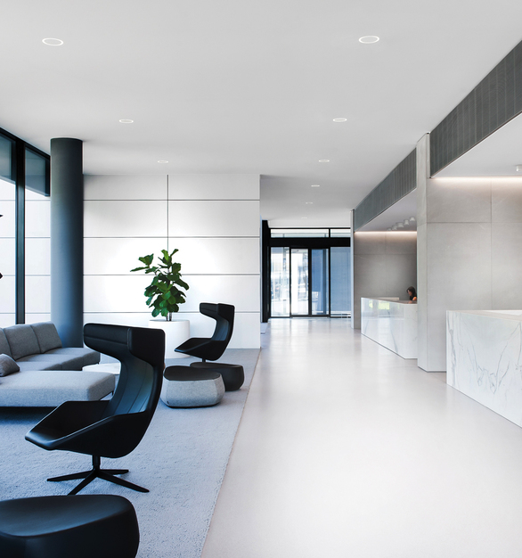 A bright and modern lobby featuring high-end finishes and furniture. We provided our Portal Recessed and Surface luminaires to complement the interior design elements.
