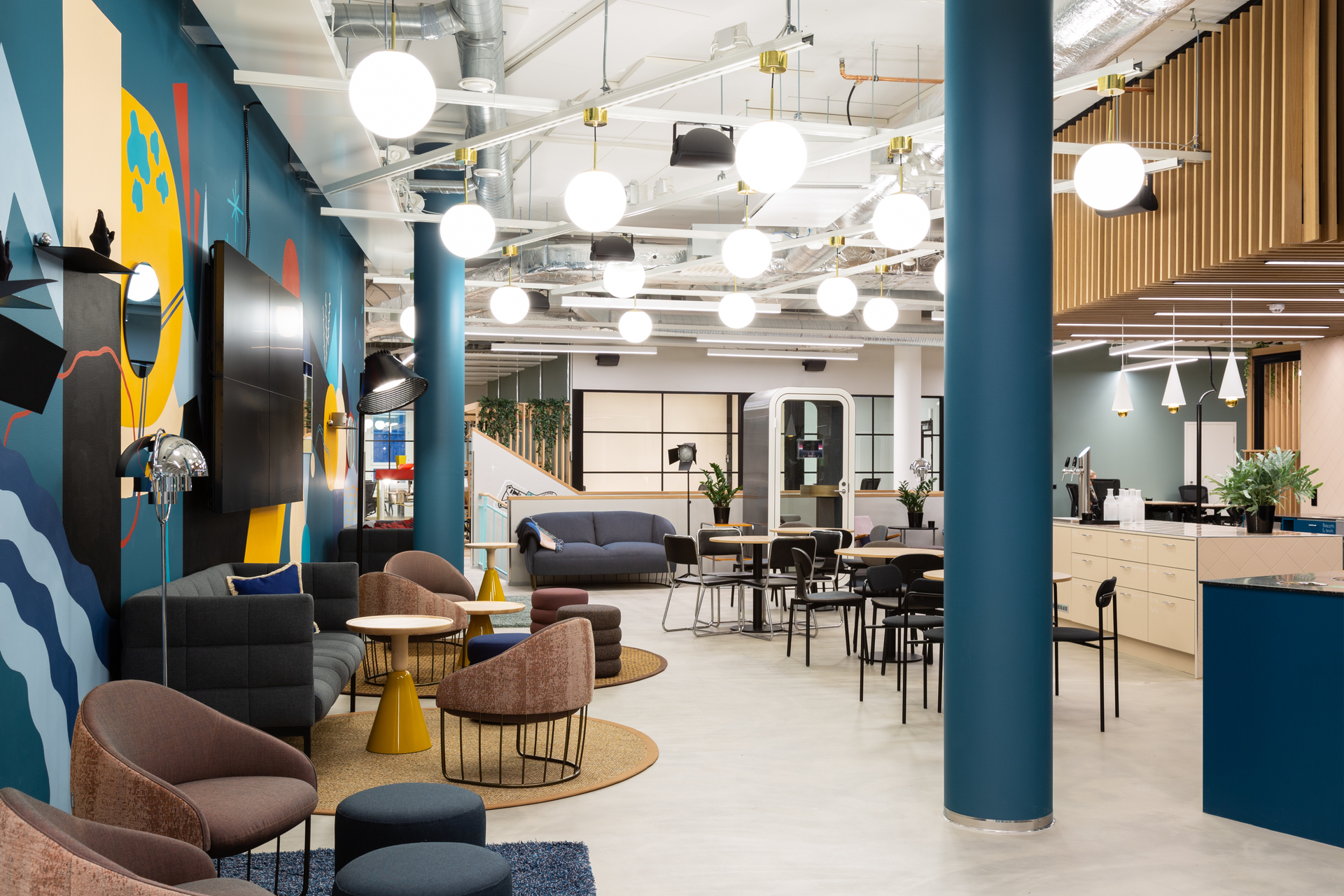 The vibrant and energetic break room and common area at MOW Supernova Coworking Offices in Tampere, Finland, featuring Framery Acoustics' Framery O office pod. Photography by Esa Kapila