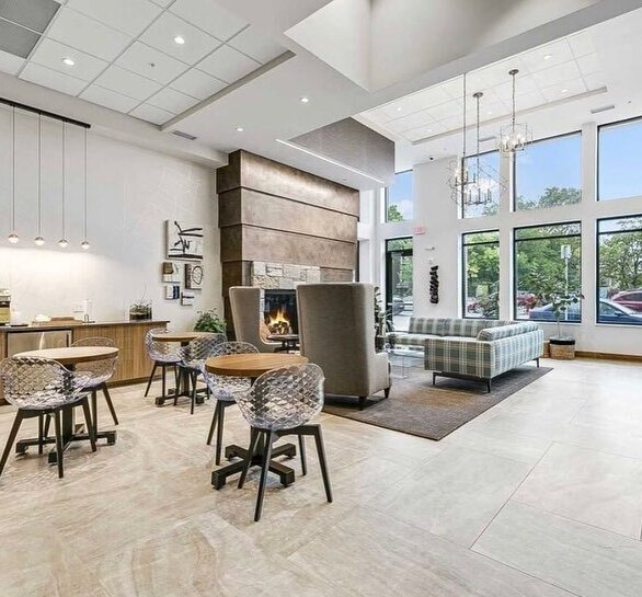 The resident community center at Rex26 in Minneapolis, MN has enough space for residents to relax on a couch or warm up a meal at one of its dining tables. Furniture was sourced by Fuse.