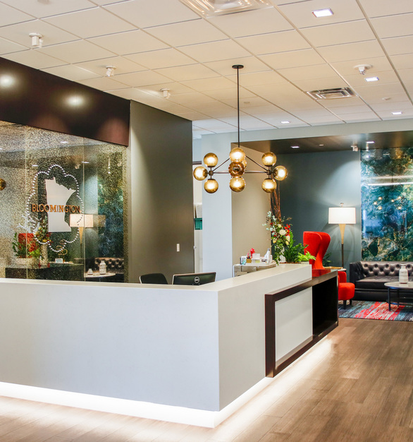 The welcoming information desk at the Bloomington Convention & Visitors Bureau features modern lighting and beautiful antique mirrored glass panels by GlassArt Design.