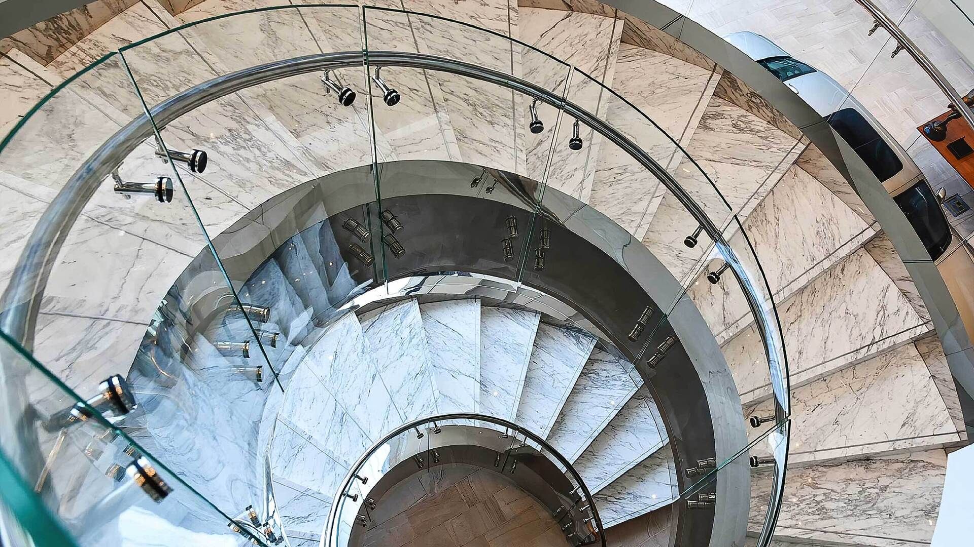 A curved staircase could be the architectural focal point in a showroom. Using bent glass balustrades (railings) allows you to create a modern architectural masterpiece that will enhance the feeling of space and light in your design.