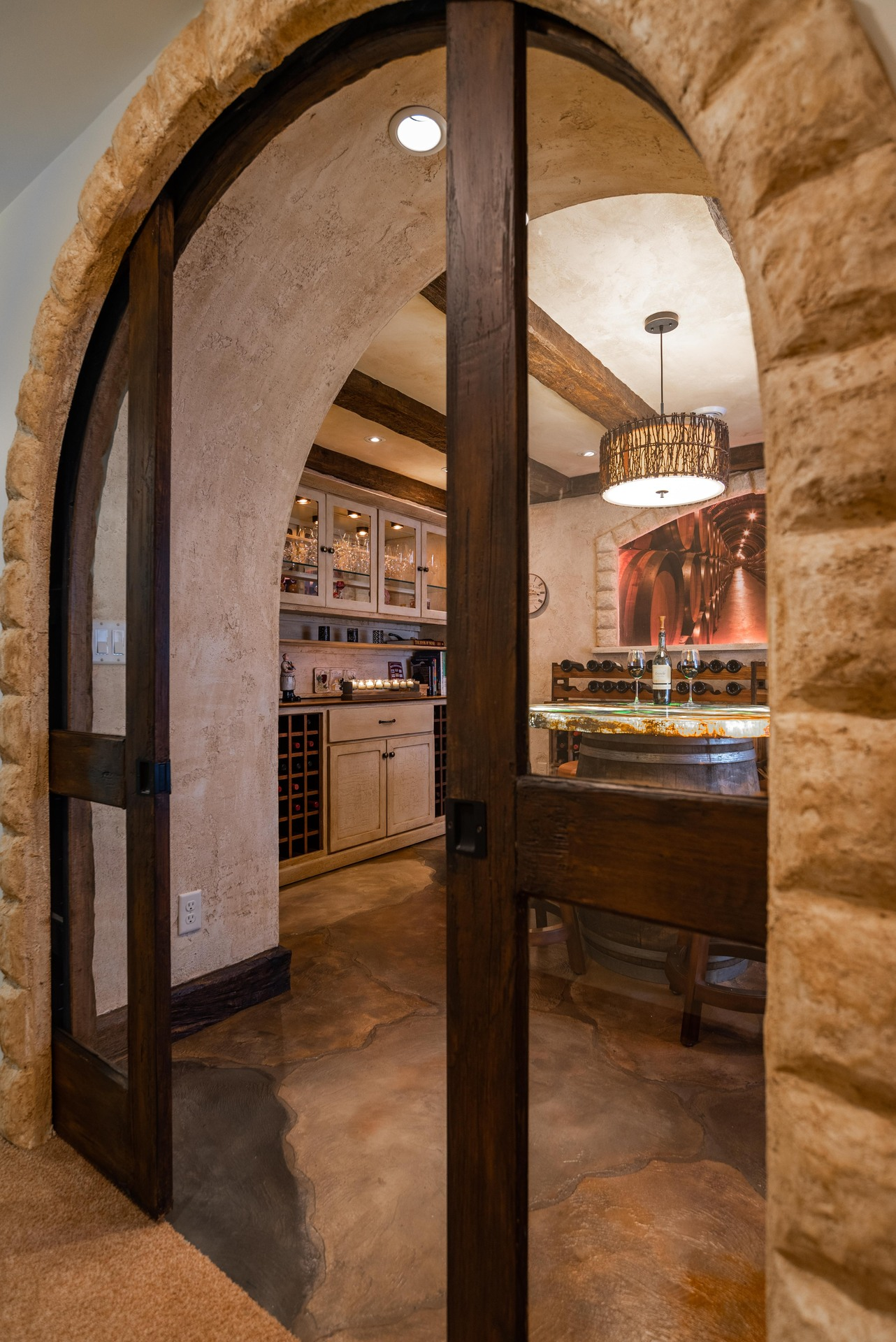 A beautiful archway leads into a wine tasting room that boasts custom flooring and tabletop by Granicrete Minnesota.   Photographer: John Walsh