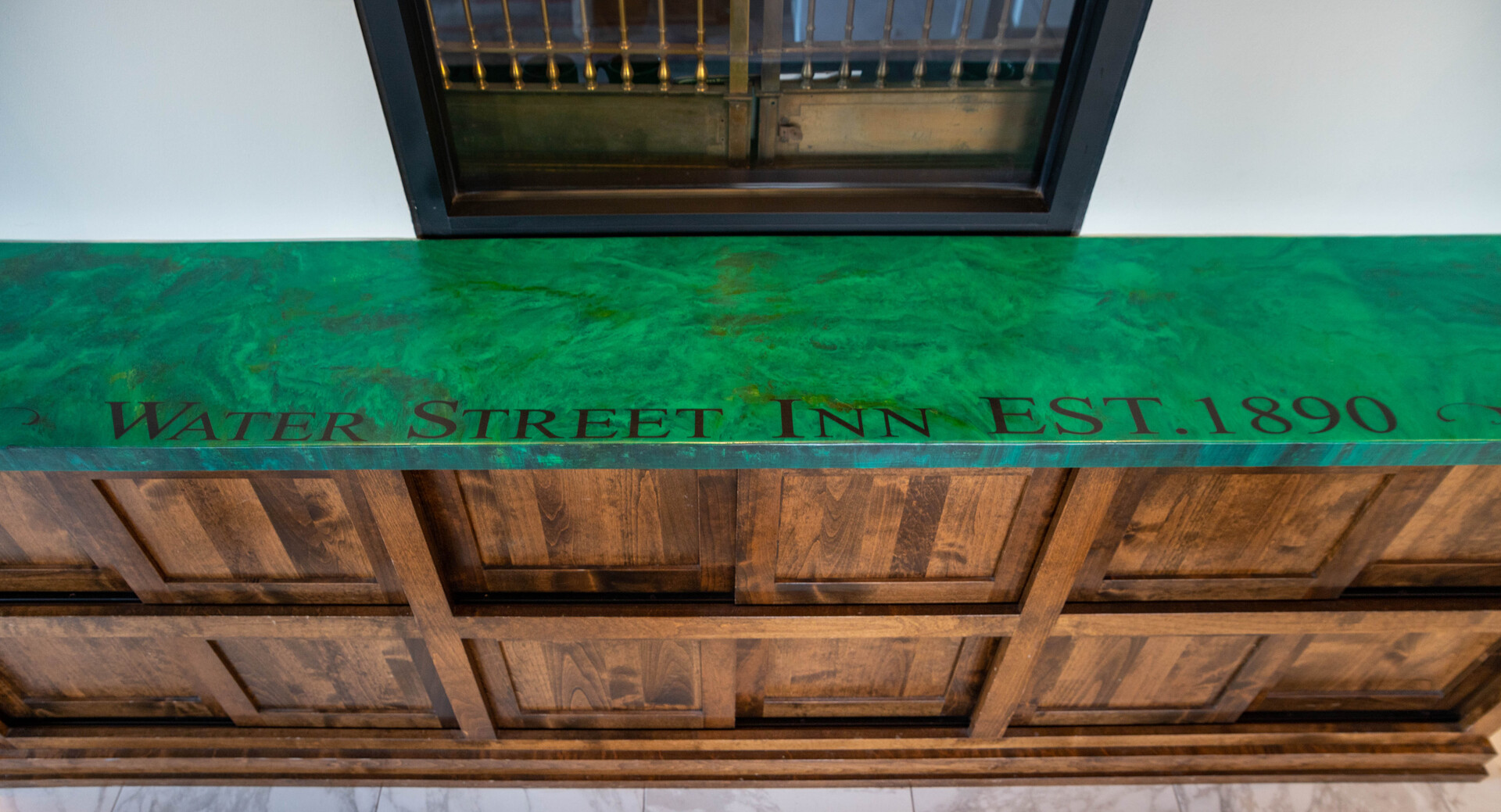Granicrete countertops can be found in two locations in the Water Street Inn's lobby. The first is the check-in desk, which boldly greets new guests with its swirled kelly green color that also features a vibrant green inlay. On the other side of the room, another Granicrete countertop is used for the coffee bar.