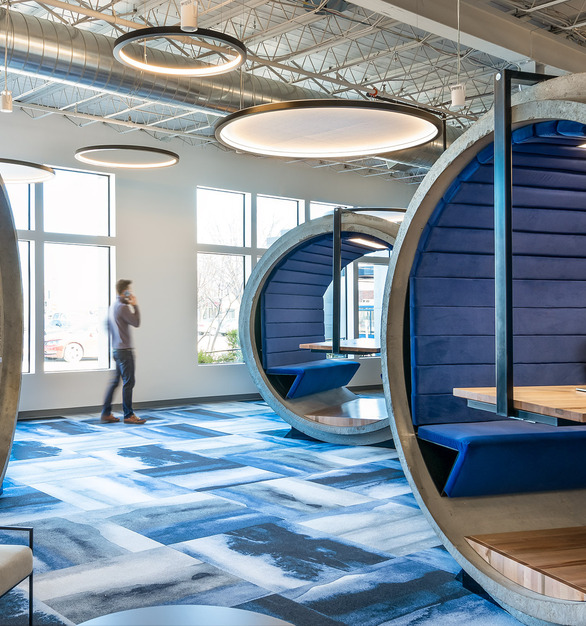 The Garney Construction Offices in Kansas City, MO feature unique circular booth seating where employees can collaborate and relax with one another. OCL Rev Acoustic hanging pendant lights help illuminate the space.