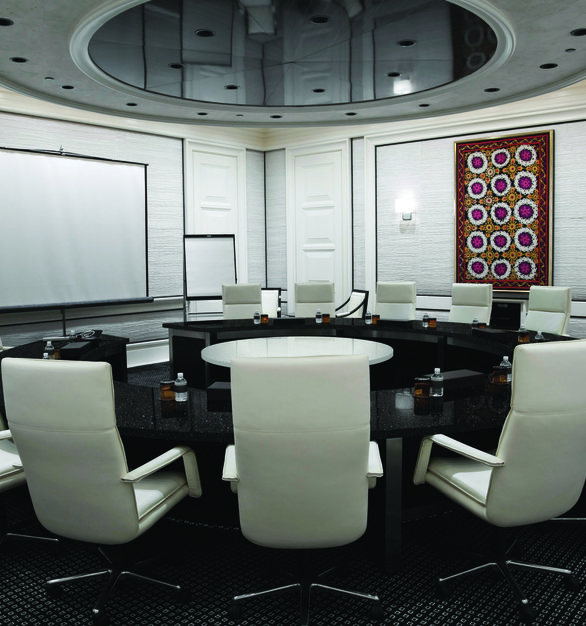 A conference room design featuring a large circular table by Hanstone Quartz in the Black Coral finish.