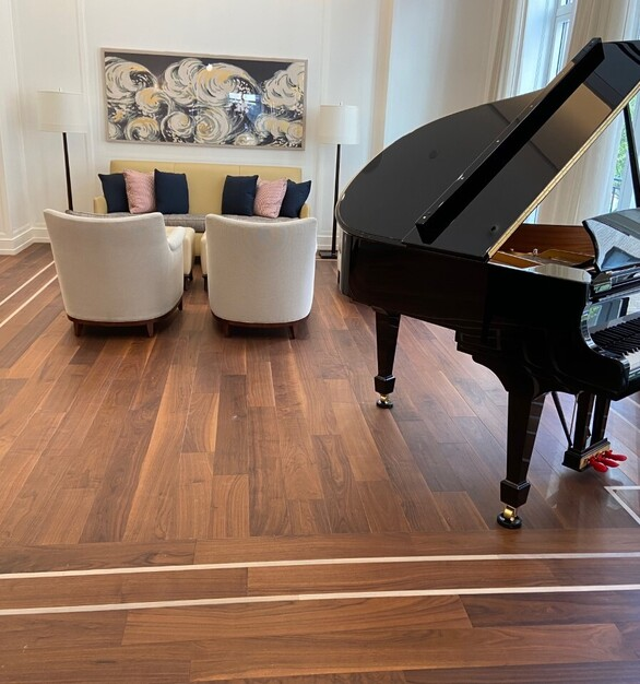 The lounge area at the senior living facility has gorgeous hardwood floor with an accent design around the corners.