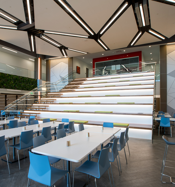 The large office atrium and common area feature various interior design elements that showcase the vibrant, engaging, and energetic colors and finishes of the company's brand. Photography by Alex Benge.