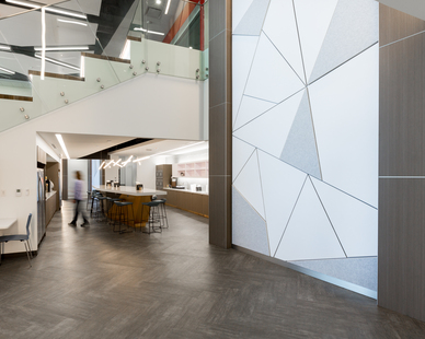 The unique wall art panels give energy and vibrancy to the transition space between the lobby and break room, while the neutral tones help achieve a comfortable open office design environment. Photography by Alex Benge.
