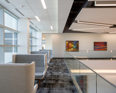 A spacious mezzanine level with comfortable seating allows co-workers to relax and wind down. The different lounge spaces give employees versatile gathering areas throughout the building, while the open office design keeps the environment airy and relaxed. Photography by Alex Benge.