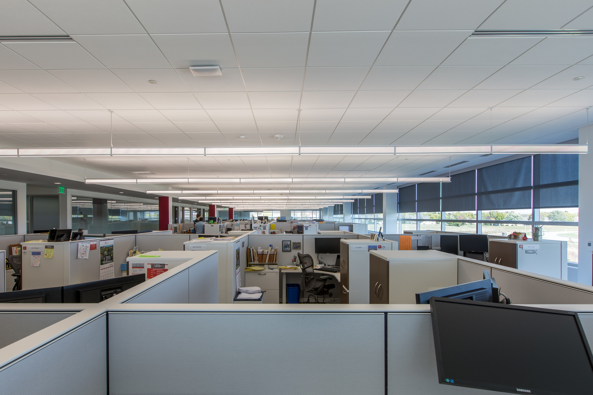The open office design allows for ample natural light through the smart shading system and expansive windows. Eye-catching pendant lights also help provide comfortable lighting throughout the building. Photography by Alex Benge.