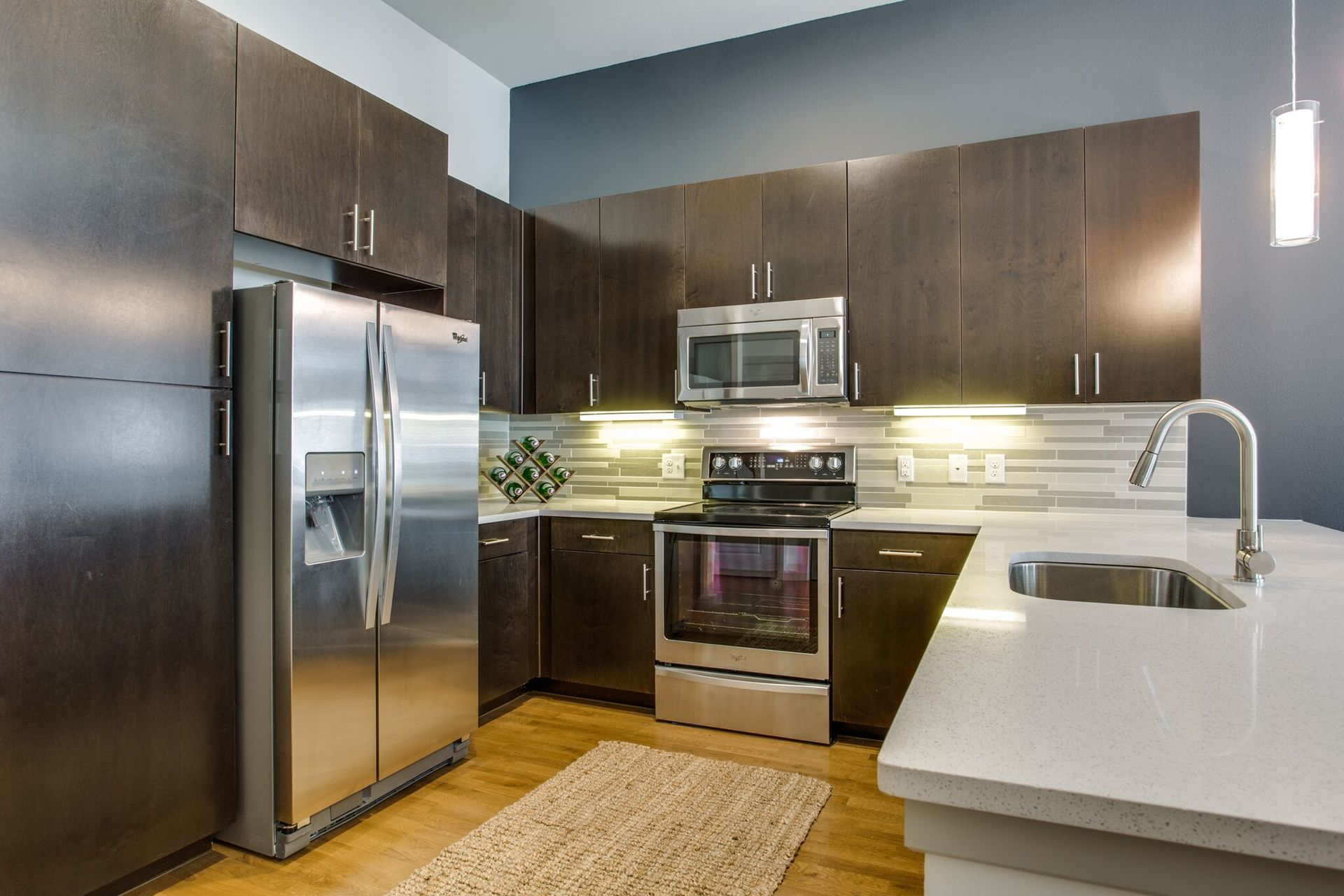 This apartment complex has kitchens that are equipped with quartz countertops and designer backsplash and  under-cabinet lighting, by Hensley Lamkin Rachel.