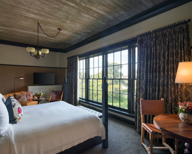 A bedroom suite design with a view at Hotel Emma in San Antonio, TX, featuring windows systems by Pella.