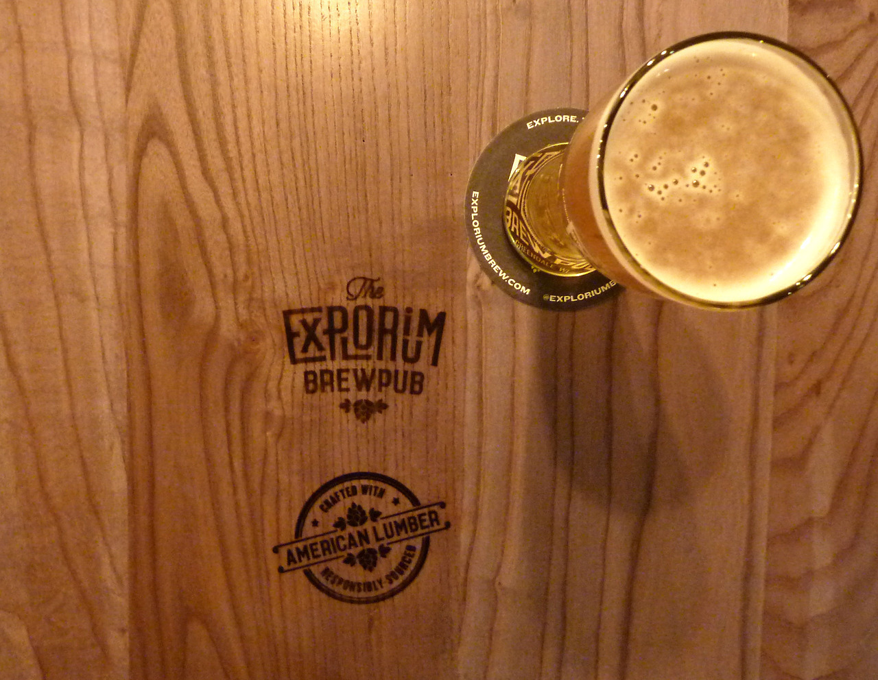 Wood branding done on a tabletop by i2i Designs at The Explorium Brewpub in Greendale, WI.