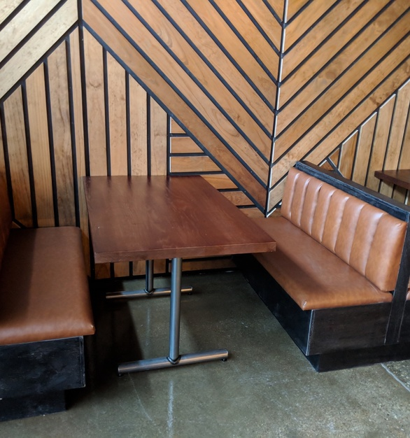 i2i Design furnished this restaurant with custom Oak tables, booth seating, and pine wall cladding.