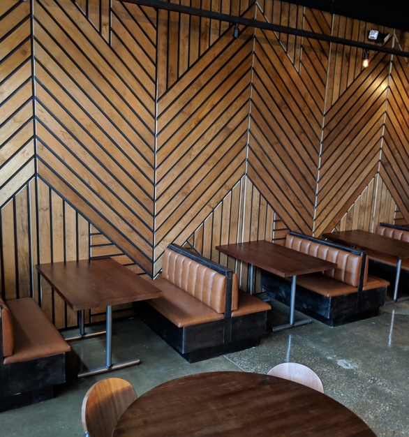 i2i Design furnished this burger joint with custom Oak tables, booth seating, and the beautiful Pine wall cladding.