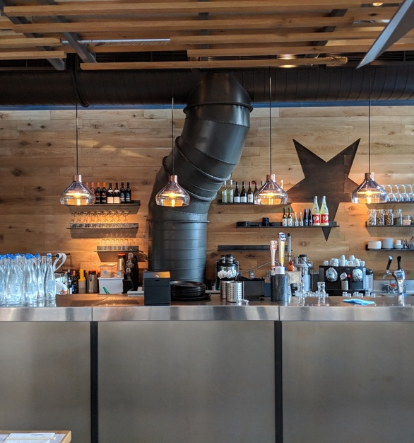 Reclaimed white oak wall cladding behind the bar with CNC routering of star logo.