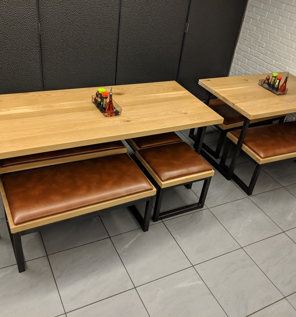 White Oak tabletops and benches with upholstered seats on custom steel square tube bases.