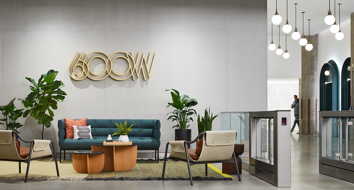 Gold custom logo signage accent the wall behind the seating area.  Retro-inspired and plants complete the space.