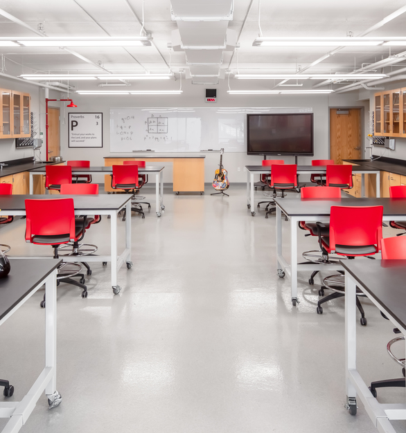 Newly designed college-level science classroom features flooring by Sherwin Williams, cabinetry and tables from Haldeman Homme, chairs from SitOnIt Seating, sourced through Fuse, chair vinyl by DesignTex, also sourced through Fuse, and a decorative element wall graphic from ASI Signage.