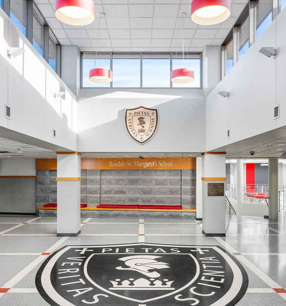 Updated school entryway features new lighting from Artemide, vibrant red cushions courtesy of Union Place, DesignTex & Fuse. Newly installed flooring from Brazzini Brothers & Company.