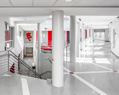 Hallway expansion and renovation features flooring from Grazzini Brothers and Company, a red knight decal from ASI Signage and a striped acoustical wall from Acoustic Associates. This hallway and stairwell leads to new additions such as classrooms and an atrium.