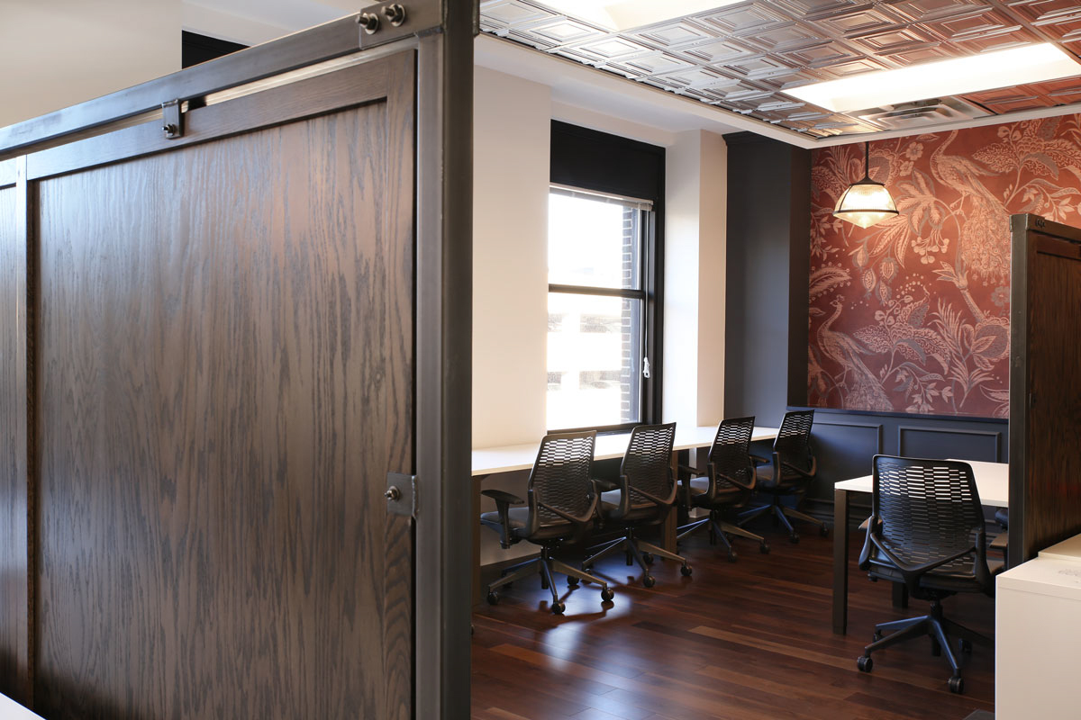 Wood flooring and an accent wall adds variety to the interior design of a space at COCO in Minneapolis, Minnesota, furnished by iSpace Environments.