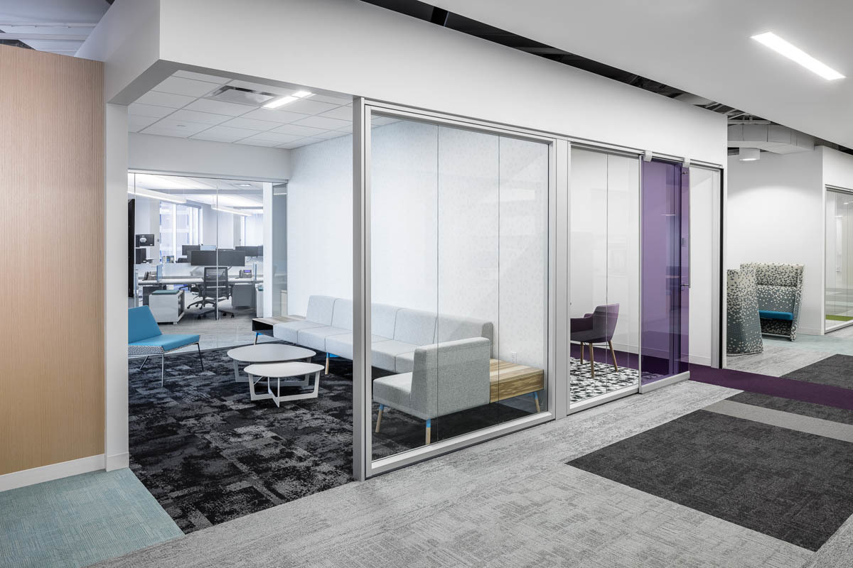 Frameless glass walls helps the space feel airy and open. Bright finishes and accent colors help elevate the interior office design.