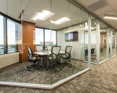 Frameless glass walls add a contemporary element to any space at ISG in Bloomington, Minnesota, furnished by iSpace Environments.