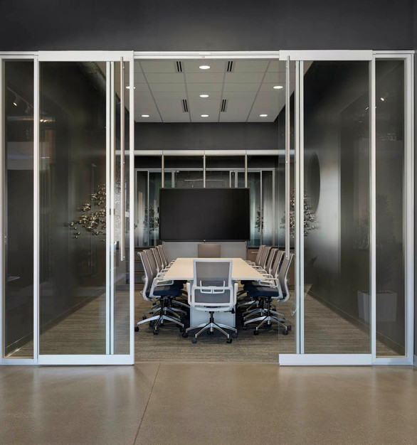 The conference room design with glass sliding doors and glass walls that create a private but open feeling design at the SVL office in Roseville, Minnesota.