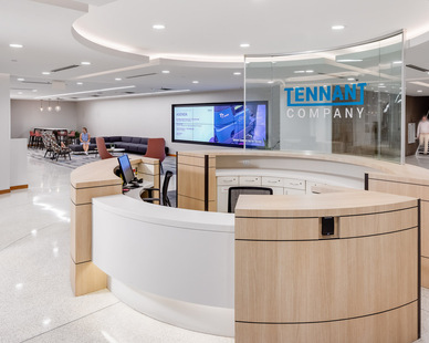 The reception desk features wood accents that promote the high-end finishes throughout the office. Tennant's branding was also incorporated on clear glass to blend in with the overall space design.